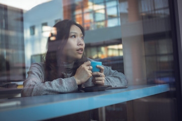 Thoughtful woman having coffee at table
