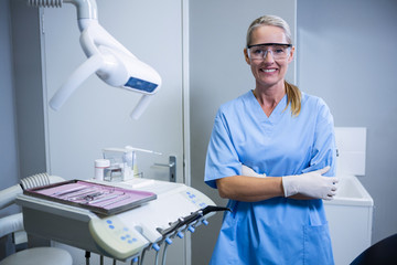 Smiling dental assistant with protective glasses