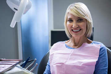Smiling patient sitting on dentist's chair