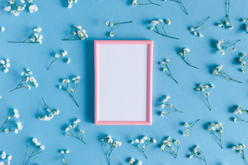 Photo frame with white paper card mockup. Floral pattern made of white gypsophila on a blue pastel background