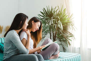 Beautiful young asian women LGBT lesbian happy couple sitting on sofa reading book together near window in living room at home. LGBT lesbian couple together indoors concept. Spending nice time at home