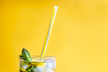 Ice tea with ice, lemon and mint on a combined colored yellow background. Summer cold drink cocktail. Copyspace