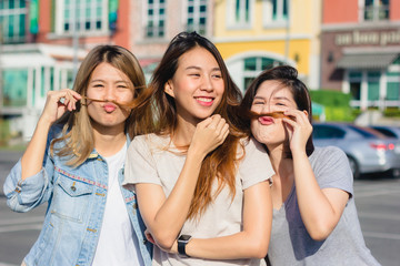 Happy young Asian women group city lifestyle playing and chatting each other among the pastel building city on weekend. City lifestyle of girls group. City lifestyle and outdoor activity concept.