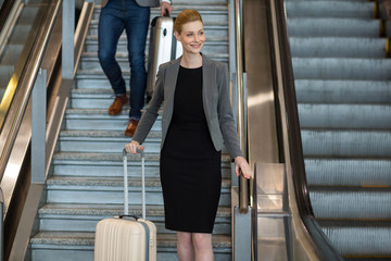 Businesswoman with luggage walking downstairs beside escalator