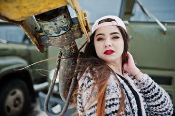 Brunette stylish casual girl in cap against old truck crane.