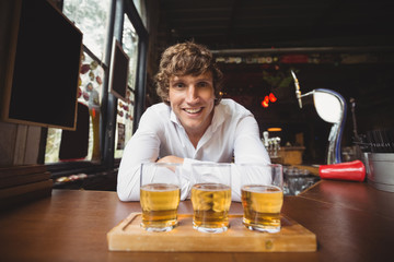 Portrait of bartender with tray of whisky shot glasses at bar counter