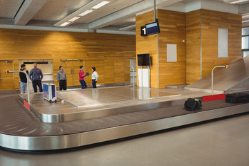 People waiting for luggage in baggage claim area