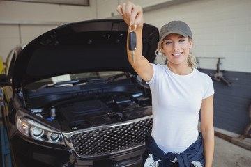 Female mechanic in garage holding car key