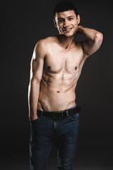 Portrait of satisfied male stripped to waist while keeping head by arm. He isolated on black background