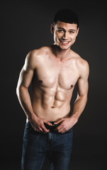 Portrait of cheerful young man with attractive body holding hands on belt. Happy bare-chested guy concept