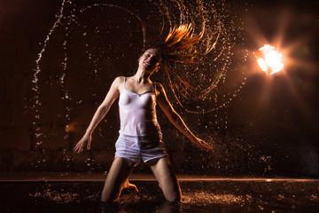 Girl in white dress in water in a dark water in pool in studio and dark background