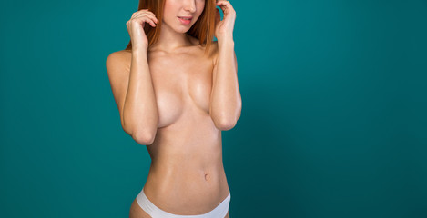 Cheerful nude girl standing with bare breast. She is touching her hair and smiling. Isolated and copy space