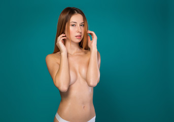 Waist up portrait of attractive young woman posing topless. She is looking at camera with confidence. Isolated and copy space