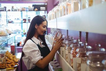 Female shopkeeper looking at turkish sweets jar on shelf