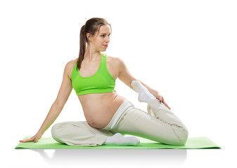 Pregnant woman making exercise, isolated on white