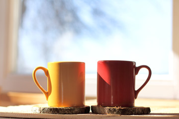sunny atmosphere of spring morning/ two mugs of a hot drink on table in the background of window with silhouette of tree and blue sky