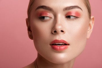 Close up of female expression with daily maquillage looking aside. Her skin having healthy tone. Isolated on rose background