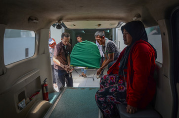 The body of man who died after consuming tainted homemade alcohol is carried by relatives into an ambulance at a hospital in Cicalengka, Bandung Regency, West Java