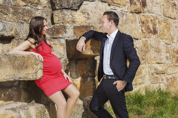 Pregnant woman and husband standing on wall