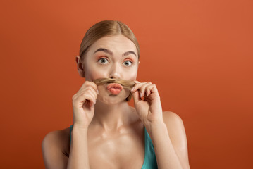 Portrait of well cared woman having fun with her lock while holding it between mouth and nose. Isolated on background