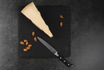 An appetizing solid cheese on a black plate on a gray stone background