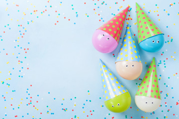 Colorful balloons and confetti on blue table top view. Birthday or party background. Flat lay. Greeting card.