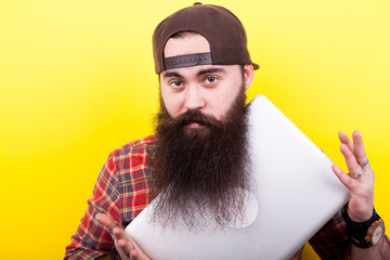 Cool hipster student with long beard and a laptop in hands on yellow background