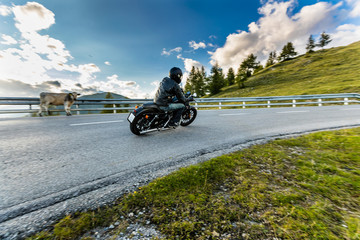 Motorcycle driver riding in Alpine highway, Nockalmstrasse, Austria, Europe.