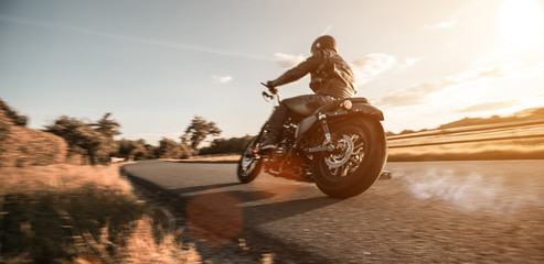 Man riding sportster motorcycle during sunset. Wall mural