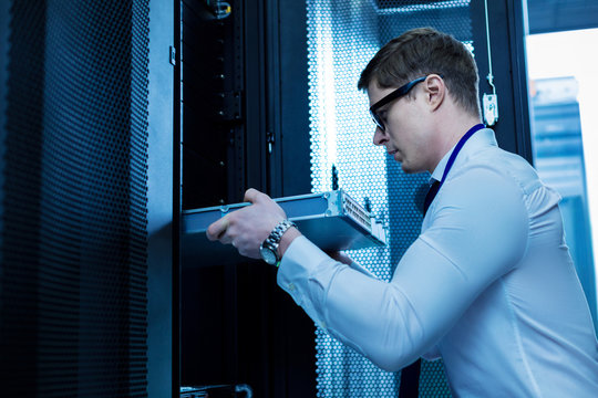Modern equipment. Serious professional operator working with server equipment in the office