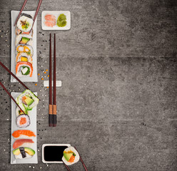 Traditional japanese sushi pieces on rustic concrete background.