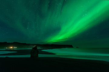 The Northern Light at the Vik Cliffs Iceland. Landscape of Vik beach; with green bands of Aurora Borealis. Night Seascape a paradise for travel and vacations.