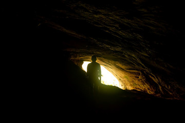 woman standing in Rawana Ella cave in Sri lanka. silhouette of man and orange light on background