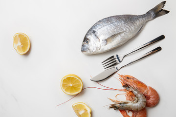 Shrimps and fish with lemon slices and cutlery isolated on white