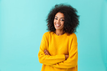 Happy brunette woman in yellow shirt looking on camera with perfect smile standing with arms crossed, isolated over blue background
