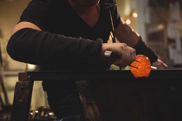 Glassblower shaping a molten glass