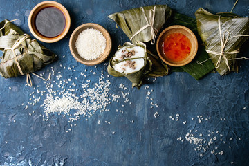 Asian rice piramidal steamed dumplings from rice tapioca flour with meat filling in banana leaves. Ingredients and sauces above over blue texture background. Top view, space.