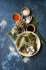 Asian rice piramidal steamed dumplings from rice tapioca flour with meat filling in banana leaves served in ceramic bowl. Ingredients and sauces above over blue texture background. Top view, space.