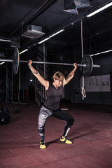 Strong woman lifting barbell as a part of crossfit exercise routine.