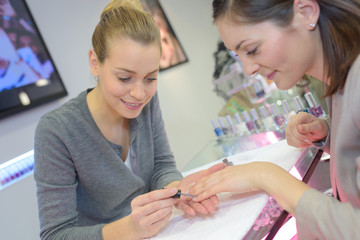 attractive nail salon worker giving a manicure her regular customer