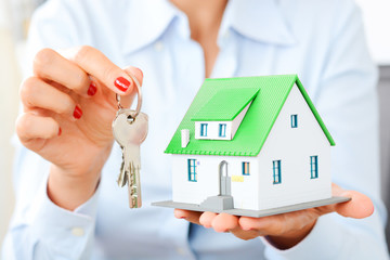 Businesswoman holding miniature house and key, real estate transaction concept