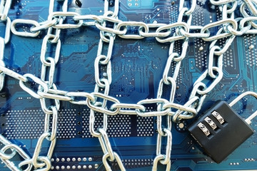 Computer mainboard with chain and padlock, information technology security concept