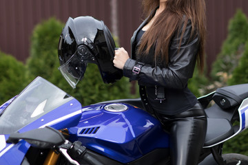 A biker girl in a leather and motorcycle.