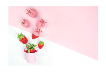 Colorful sweet tasty food concept with strawberries and small bucket on white and pink background. minimalistic original fruit idea, copy space.
