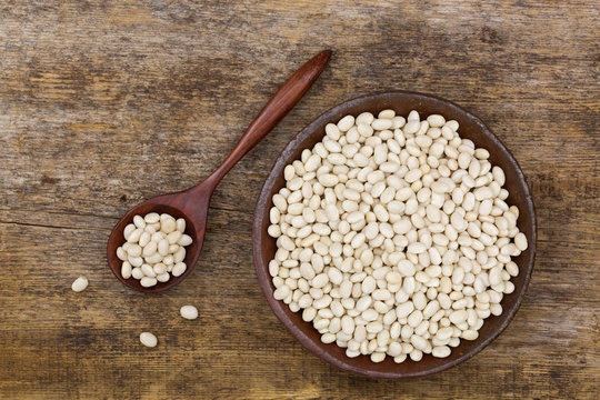 White pea beans, also called Navy bean, Pearl Haricot, Boston bean in clay bowl on wood