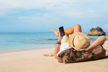 Guy with smartphone lying on the beach Wall mural