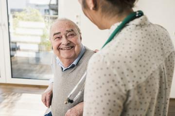Senior man smiling at nurse at home
