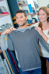 Couple in clothes shop, holding jumper against man