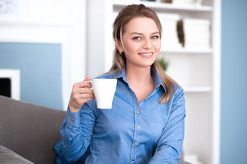 Cute girl smiling, holding coffee in hand and looking at you