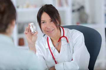 pretty female doctor showing pills to patient